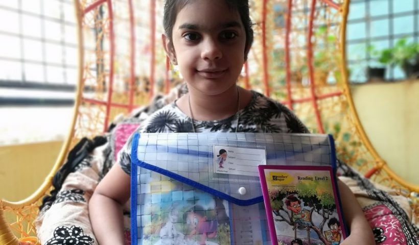 a girl holding a English Phonics learning kit